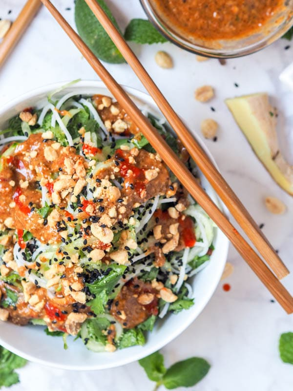 vegan asian noodle salad with dressing, sriracha and crushed peanuts